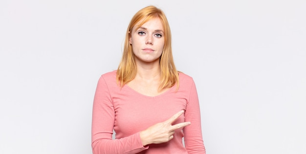 Una bella donna dai capelli rossi che si sente felice, positiva e di successo, con la mano che forma una v sul petto, mostrando vittoria o pace