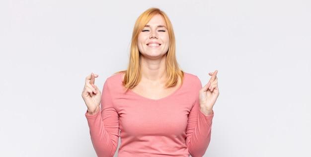 Bella donna dai capelli rossi che si sente nervosa e piena di speranza, incrociando le dita, pregando e sperando in buona fortuna