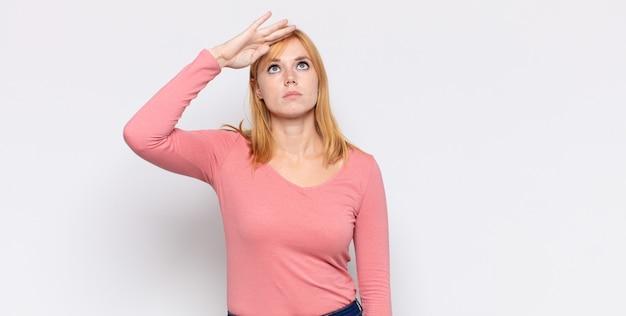 Donna graziosa dalla testa rossa che saluta la telecamera con un saluto militare in un atto di onore e patriottismo, mostrando rispetto