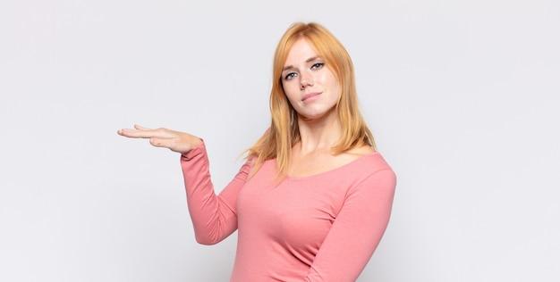 Donna graziosa capa rossa che tiene un oggetto con entrambe le mani sullo spazio della copia laterale, mostrando, offrendo o pubblicizzando un oggetto