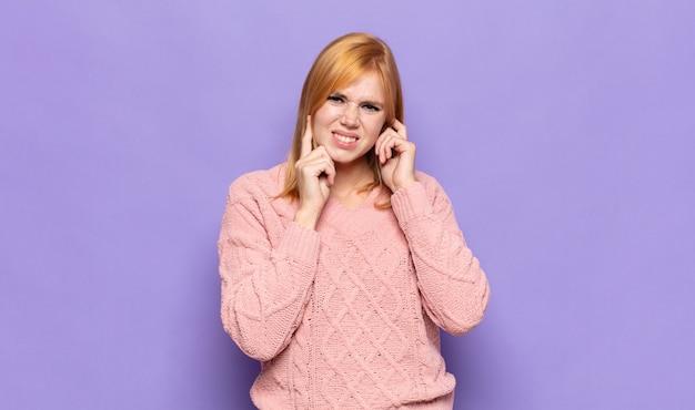 Bella donna dai capelli rossi che sembra arrabbiata, stressata e infastidita, coprendo entrambe le orecchie con un rumore assordante, un suono o una musica ad alto volume