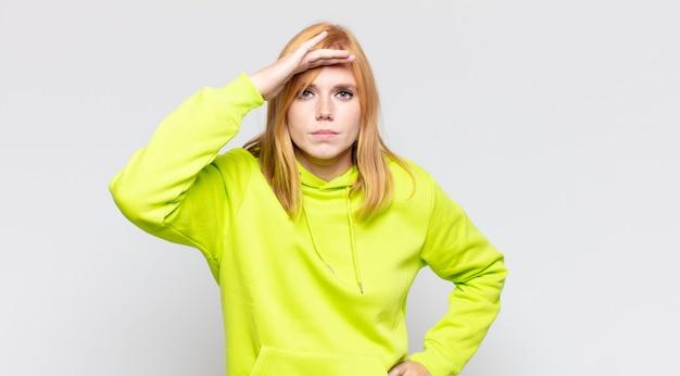 Bella donna dai capelli rossi che sembra sconcertata e stupita, con la mano sulla fronte che guarda lontano, guardando o cercando