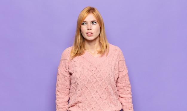Bella donna dai capelli rossi che sembra perplessa e confusa, mordendosi il labbro con un gesto nervoso, non conoscendo la risposta al problema