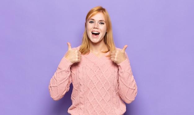 Donna graziosa capa rossa che sorride largamente felice, positiva, sicura e di successo, con entrambi i pollici in su