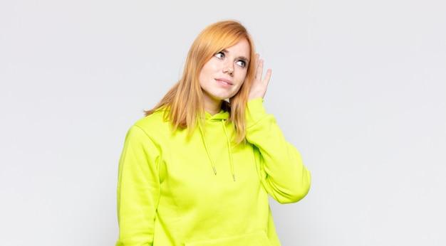 Bella donna dai capelli rossi che sorride, guarda con curiosità di lato, cerca di ascoltare i pettegolezzi o di sentire un segreto