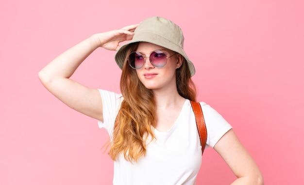 Turista graziosa dalla testa rossa che si sente perplessa e confusa, grattandosi la testa