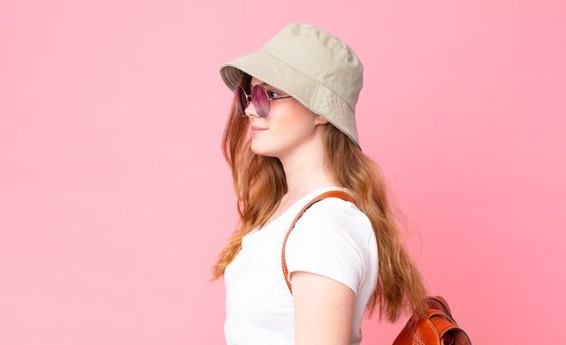 Turista graziosa dalla testa rossa sulla vista di profilo pensando, immaginando o sognando ad occhi aperti