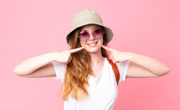 Turista graziosa dalla testa rossa che sorride con sicurezza indicando il proprio ampio sorriso