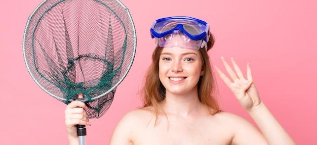 Donna dai capelli rossi sorridente e dall'aspetto amichevole, che mostra il numero quattro con gli occhiali e una rete da pesca Foto Premium