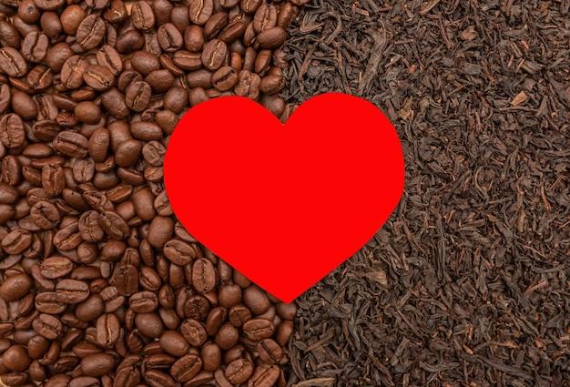 Cuore rosso su uno sfondo di chicchi di caffè tostati e foglie di tè nero secco, vista dall'alto da vicino