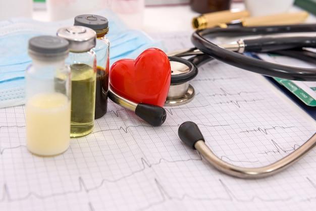 Cuore rosso su cardiogramma con fiale e stetoscopio