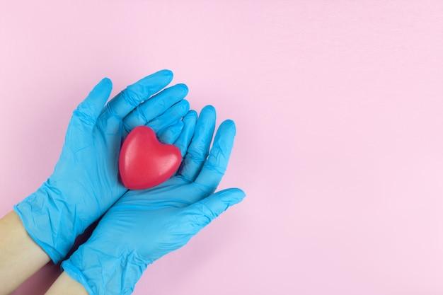 Cuore rosso sulle mani del medico, diagnosi medica e storia del concetto di pazienti.