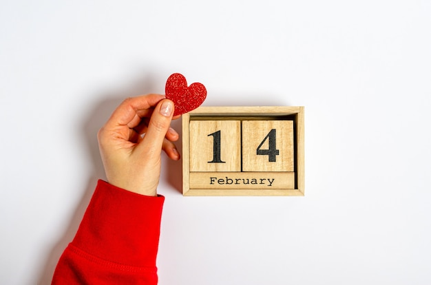 Cuore rosso in una mano femminile vicino a un calendario in legno con la data del 14 febbraio