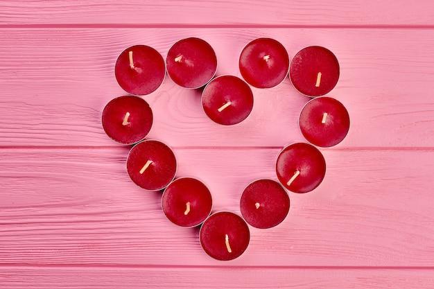 Cuore rosso dalle candele, vista dall'alto. piccole candele rosse disposte a forma di cuore su fondo di legno rosa con spazio di copia. concetto di amore e romanticismo.