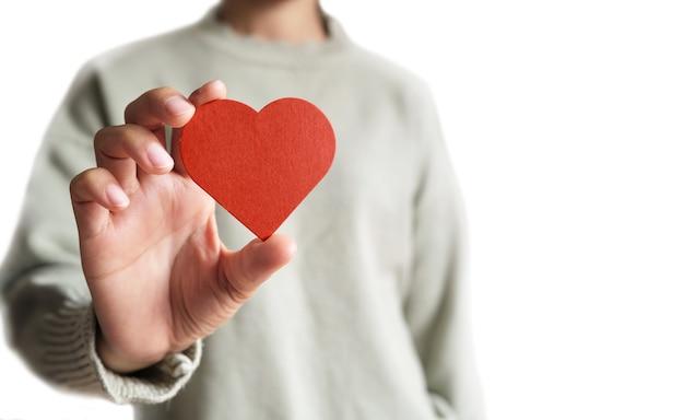 Cuore rosso sulla mano della ragazza. simbolo di sostegno che esprime amore. prendersi cura, giorno di san valentino e giornata mondiale del cuore, concetto di salute del cuore