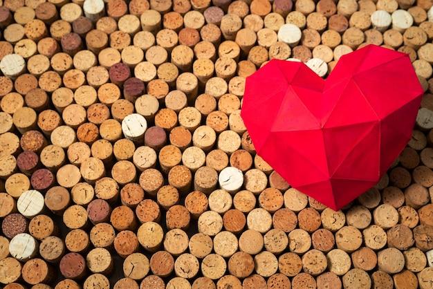 Il cuore rosso giace su tappi per vino, design di sfondo creativo, spazio per il testo