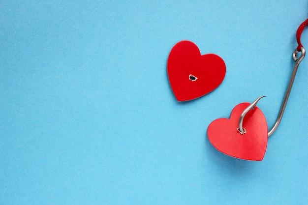 Un cuore rosso su un amo da pesca in metallo su un blu