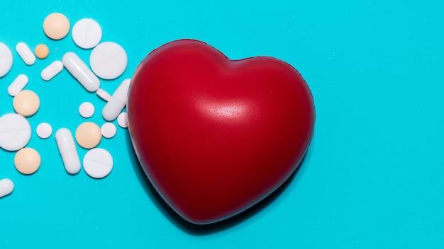 Cuore rosso e pillole su sfondo blu