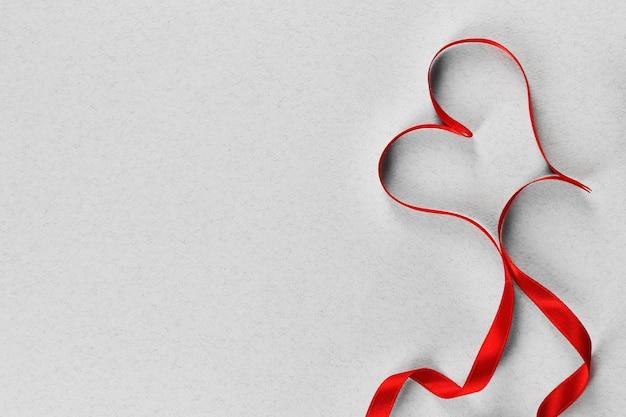 Nastro cuore rosso su sfondo grigio chiaro strutturato