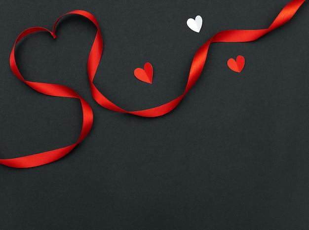 Cuore rosso a forma di nastro e cuori di carta su sfondo nero con copia spazio per san valentino e matrimonio.