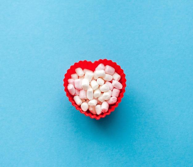 Ciotola a forma di cuore rosso con marshmallow, vista dall'alto