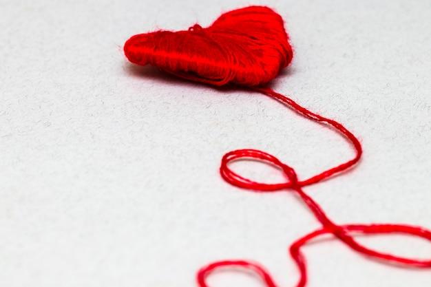 Simbolo a forma di cuore rosso realizzato in lana isolato su sfondo bianco