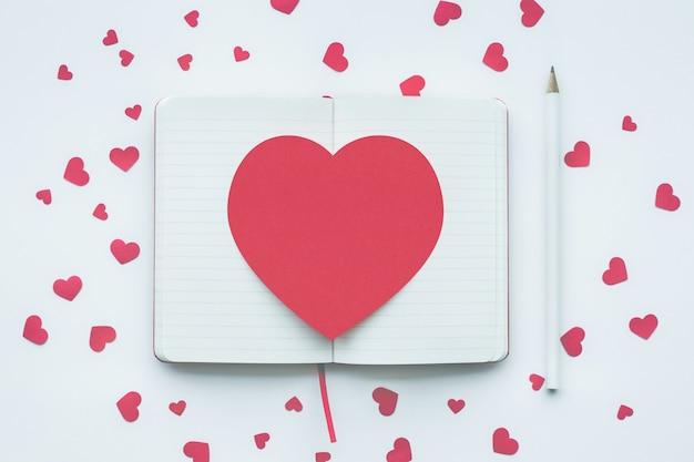 Forma di cuore rosso sul blocco note bianco