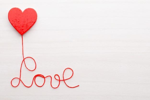 Forma di cuore rosso con nastro su fondo in legno. concetto di san valentino