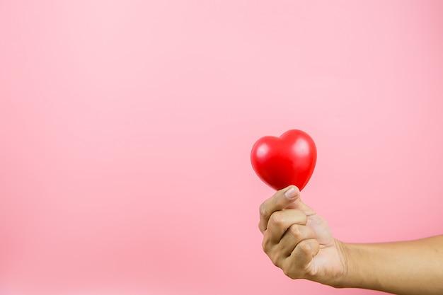 Un palloncino a forma di cuore rosso in mano contro uno sfondo rosa.