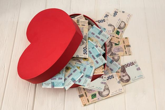 Una scatola rossa a forma di cuore piena di soldi. uah money of ukraine 1000 e 500 banconote su deskv