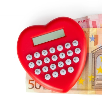 Calcolatrice a forma di cuore rosso con banconote in euro.