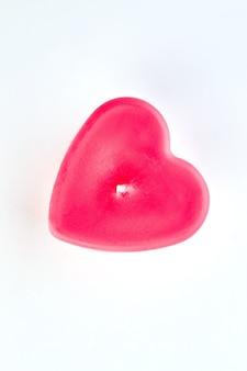 Candela a forma di cuore rosso, vista dall'alto. candela rossa a forma di cuore su sfondo bianco per la decorazione di san valentino.