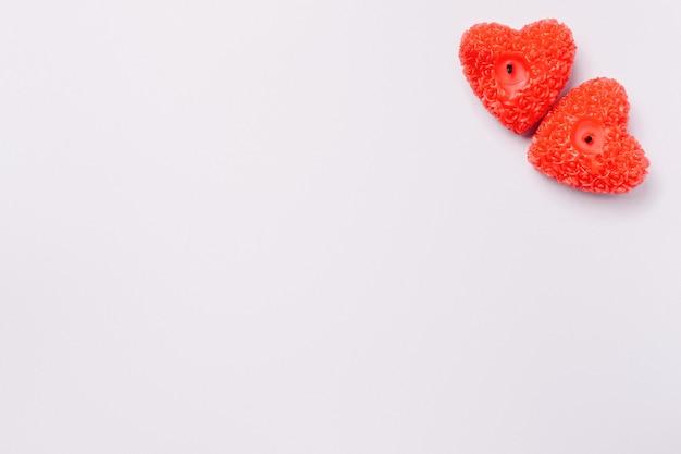 Candele rosse a forma di cuore nell'angolo su fondo grigio finale con spazio vuoto per la tua pubblicità.