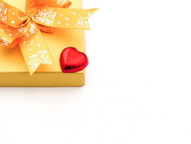Una caramella al cioccolato rossa a forma di cuore e una scatola regalo