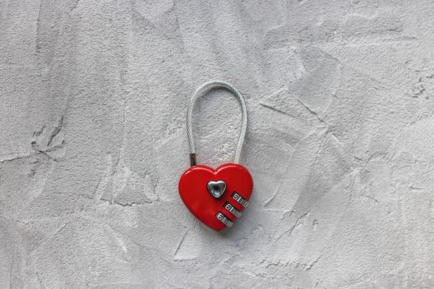 Lucchetto a forma di cuore rosso o serratura dell'amore su sfondo grigio, serratura per coppia di sposini a ponte, recinzione, cancello. oppure lucchetto a combinazione di sicurezza per valigia o bicicletta. primo piano spazio copia, viaggi e concetto di amore