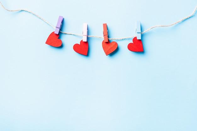 Decorazione di san valentino a forma di cuore rosso da appendere con clip in legno per amore felice sul biglietto di auguri in corda