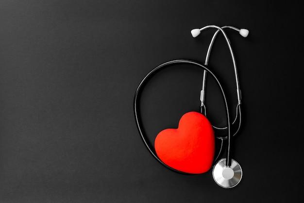 Cuore rosso e stetoscopio su carta nera. elementi essenziali distesi per il medico che utilizzano il trattamento e la cura del paziente in ospedale.