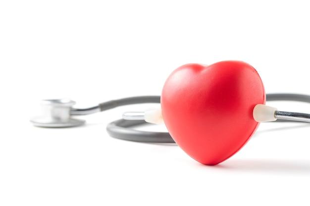 Cuore rosso e stetoscopio isoalted, concetto di assistenza sanitaria.