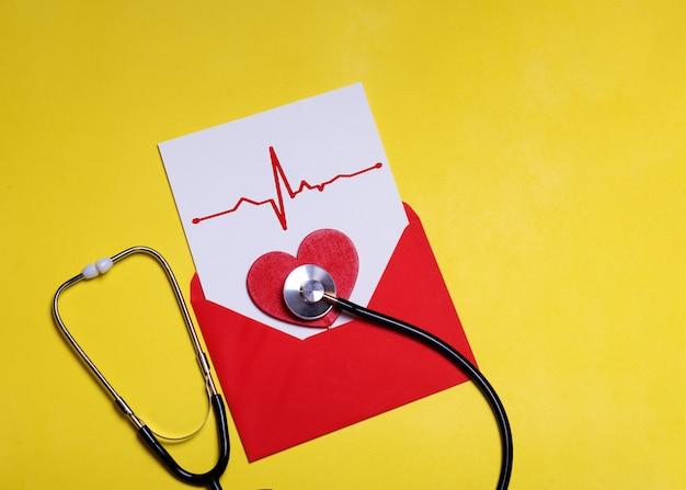 Cuore rosso e stetoscopio su carta bianca con grafico a cuore in busta rossa su sfondo giallo