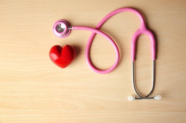 Cuore rosso e stetoscopio su fondo di legno. concetto di assistenza sanitaria