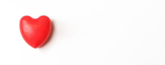Cuore rosso su sfondo bianco. amore, cura e concetto di san valentino. idea per la giornata mondiale della salute del cuore.