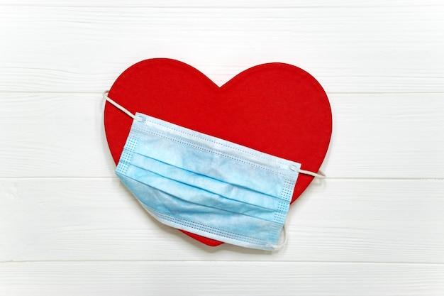 Cuore rosso con maschera protettiva usa e getta blu sul tavolo bianco. san valentino nella nuova normale pandemia