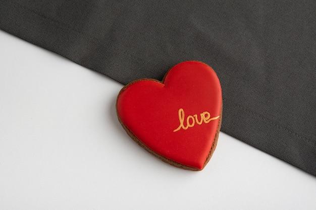 Cuore rosso con la scritta love su uno sfondo grigio e bianco. san valentino