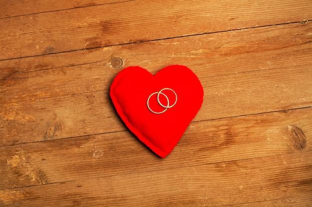 Un cuore rosso con anelli di matrimonio d'oro su un tavolo di legno