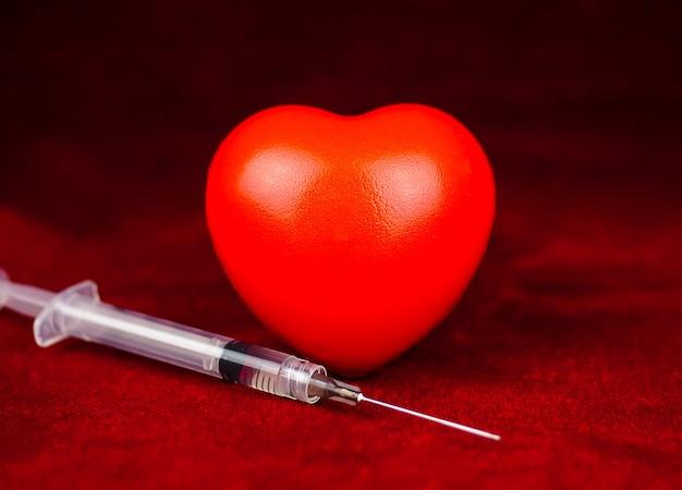 Cuore rosso con la siringa sul concetto di sfondo rosso scuro 3d della giornata della salute carità amore assistenza sanitaria