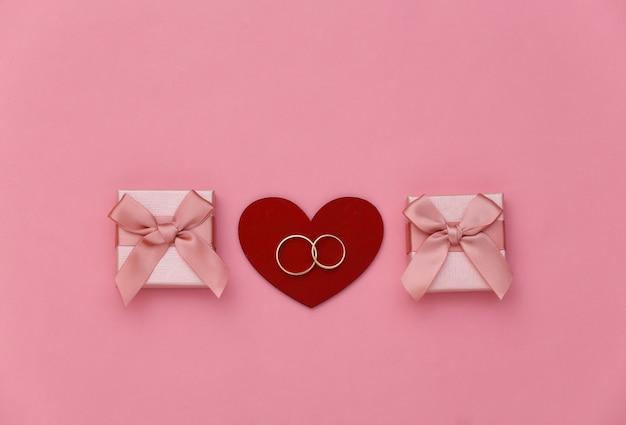 Cuore rosso con due anelli d'oro e scatole regalo su sfondo rosa.