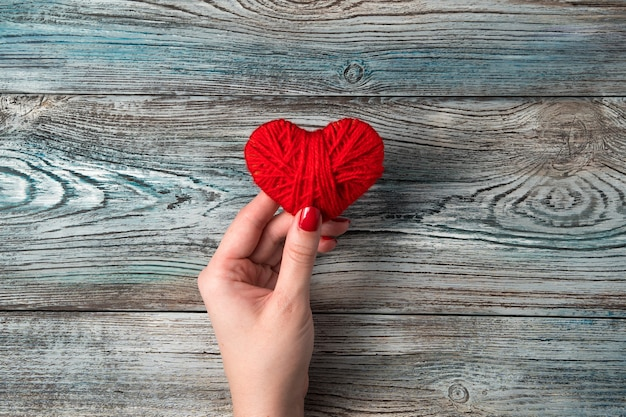 Un cuore rosso nella mano di una donna sopra un tavolo di legno grigio-blu.