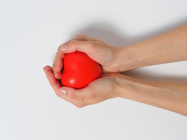 Cuore rosso nelle mani delle donne isolato su uno sfondo bianco. concetto di carità, salute e amore
