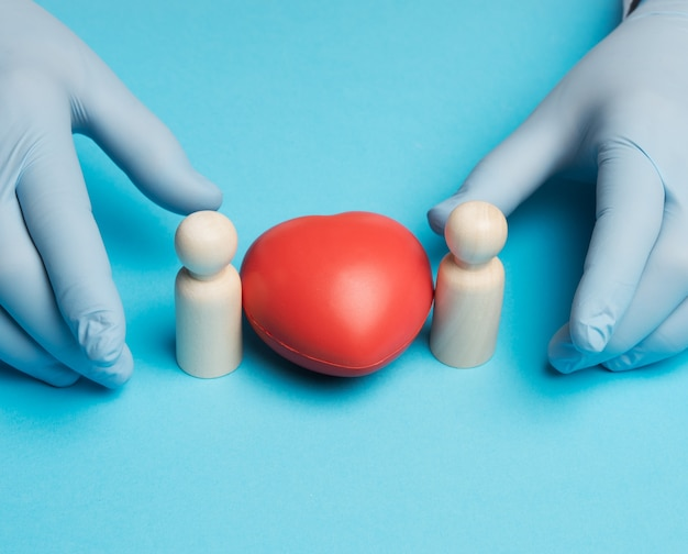 Cuore rosso e figurine di legno di una famiglia, mani del medico in guanti blu, primi piani