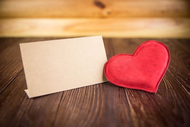 Cuore rosso sulla tavola di legno